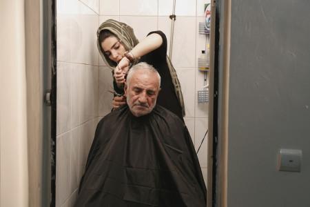 Massoumeh coupe les cheveux de son päre dans son salon situÇ dans le quartier Shoush au sud de TÇhÇran dans le film Salon de beautÇ de Shiva Sanjari ∏ ALEGRIA PRODUCTIONS